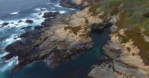 Golven die op rotsen langs de kust 4k 24fps verpletteren van Californië stock footage