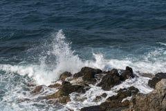 Golven die op rotsen verpletteren royalty-vrije stock fotografie