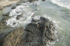 Golven die op rotsen verpletteren stock afbeelding