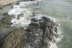 Golven die op rotsen verpletteren stock afbeeldingen
