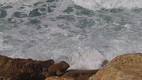 Golven die op stenen bij het strand in Tel Aviv verpletteren stock footage