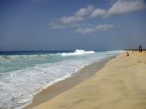 Golven die op tropisch strand met geel zand breken Stock Afbeeldingen