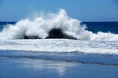 Golven die over een kei in de oceaan verpletteren Stock Afbeeldingen