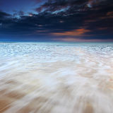 Golven die over het strand bij zonsopgang stromen Royalty-vrije Stock Afbeelding