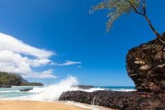 Golven die over lavarots bespatten op mooi zandig tropisch strand Stock Afbeeldingen