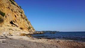 Golven die rotsen op strand raken stock footage