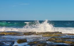 Golven die tegen de rotsen als ander broodje binnen met schepen op de oceaanhorizon bespatten stock afbeelding