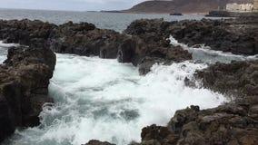 Golven die tegen de rotsen verpletteren stock footage