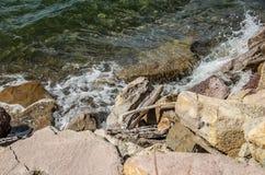 Golven die tegen rotsen bespatten Stock Afbeeldingen