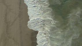 Golven die tegen rotsen op het strand verpletteren stock video