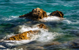 Golven die tegen rotsen op overzees verpletteren Stock Fotografie