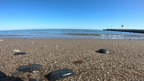 Golven die zacht op stil zandig strand verpletteren stock video