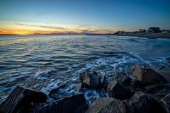 Golven en een pier bij zonsondergang in de Atlantische Oceaan in Edisto Beac Stock Foto's