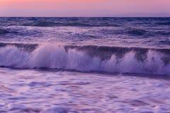 Golven en meerschuim op de zonsondergang Royalty-vrije Stock Foto's