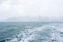 Golven en regendruppels in overzees met berg en wolk Royalty-vrije Stock Afbeelding