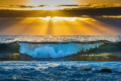 Golven onder een kleurrijke hemel bij zonsondergang stock foto's