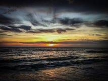 Golven onder een zonsonderganghemel Stock Afbeeldingen