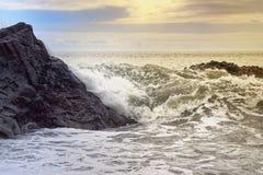 Golven op de rotsachtige kust bij gouden uur stock afbeeldingen
