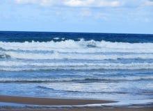 Golven op een blauwe overzees en een hemel met wolken Stock Foto's