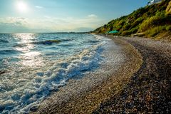 Golven op een Grieks Kiezelsteenstrand op Helder Sunny Day During de Vakantie royalty-vrije stock foto's
