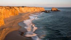 Golven op een strand met hoge klippen bij zonsondergang Royalty-vrije Stock Foto's