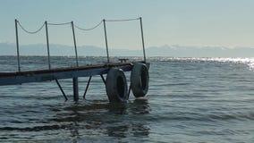 Golven op meer Meer Baikal, Siberië, houten pijler Een zonnige dag bergenhorizon stock video