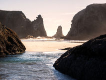 Golven op zandig strand met rotsstapels Stock Foto