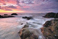 Golven, rotsen en zonsondergang Stock Foto