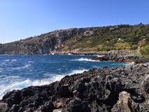 Golven tegen rotsen in Italië stock afbeelding