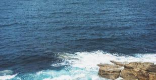 Golven van blauwe oceaanstrijd over steenachtig kustlandschap Achtergrondoverzees scape Van de het perspectiefmening van de panor royalty-vrije stock fotografie