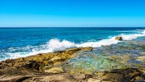 Golven van de Vreedzame Oceaan die op de rotsachtige oever van de westkust van het Eiland Oahu verpletteren stock foto's