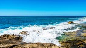 Golven van de Vreedzame Oceaan die op de rotsen op de oever van Ko Olina op het Eiland Oahu verpletteren stock afbeelding