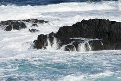Golven, water die in rotsen in het overzees verpletteren Stock Foto's