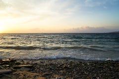 Golvend seaview van zonsondergang toneelcopyspace en rotsstrand met mooie schaduwen van gele en blauwe hemelachtergrond Stock Foto's