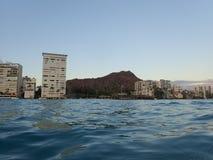 Golvend water op oceaan van Kaimana-Strand met hotels en flatgebouwen met koopflats Stock Afbeelding