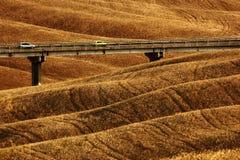 Golvende breownheuveltjes, zeuggebied, landbouwlandschap, brug met twee auto's, aardtapijt, Toscanië, Italië Royalty-vrije Stock Fotografie