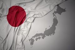 Golvende kleurrijke nationale vlag en kaart van Japan stock foto's