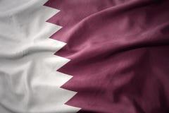Golvende kleurrijke vlag van Qatar Stock Foto