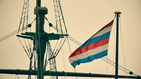 Golvende Marinevlag van de Secretaresse van Defensie van Nederland op de mast van een oud schipgedenkteken in Amsterdam stock videobeelden