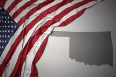 Golvende nationale vlag van de Verenigde Staten van Amerika op een grijze de kaartachtergrond van de staat van Oklahoma royalty-vrije stock afbeelding
