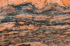 Golvende textuur van de rode tint van de granietsteen en donkere strepen Stock Foto