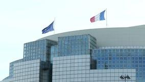 Golvende vlaggen van Frankrijk en de Europese Unie op het dak van een modern gebouw in Parijs stock footage