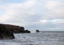 Golvenneerstorting op de rotsen stock foto's