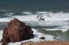 Golvenneerstorting op klippen stock fotografie