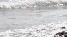 Golvenneerstorting over een rotsachtig strand stock footage