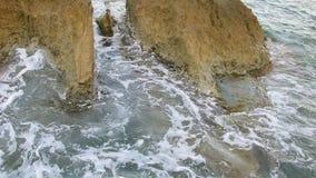 Golvenneerstorting tegen de rots op het overzees stock footage