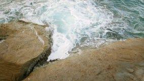 Golvenneerstorting tegen de rots op het overzees stock videobeelden