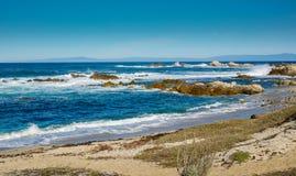 Golvenonderbreking in rotsachtige inham en zandig strand onder blauwe hemel Stock Afbeeldingen
