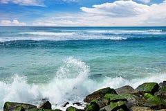 Golvenonderbreking tegen steenachtige kust van oceaan stock fotografie