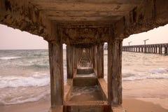 Golvenoverzees en strand onder de brug stock foto's